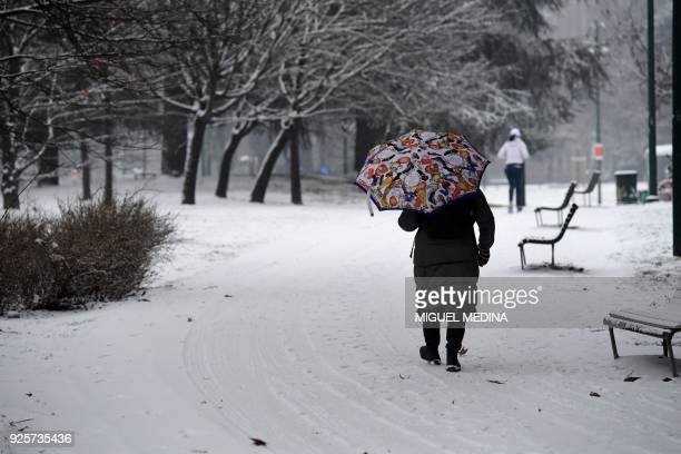 A woman walks with an umbrella in Sempione garden after snowfall in Milan on March 1 2018 Fresh heavy snowfalls and icy blizzards were expected to...