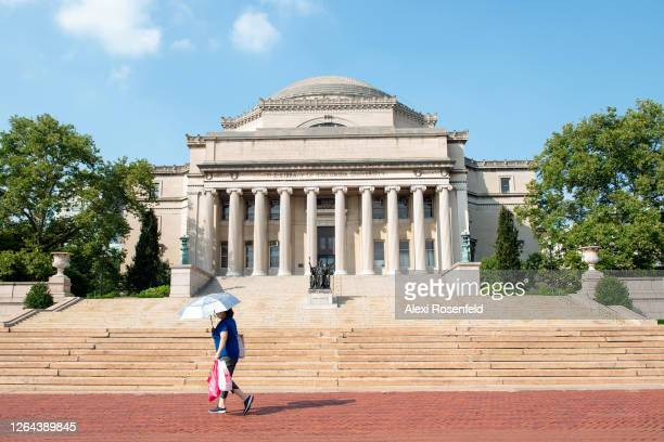 Woman walks with an umbrella in-front of the Alma Mater statue at Columbia University as the city continues Phase 4 of re-opening following...