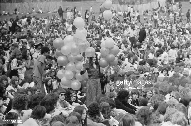 A woman walks with balloons through a crowd of pop and music fans attending the Crystal Palace Garden Party in Crystal Palace Park south London on...