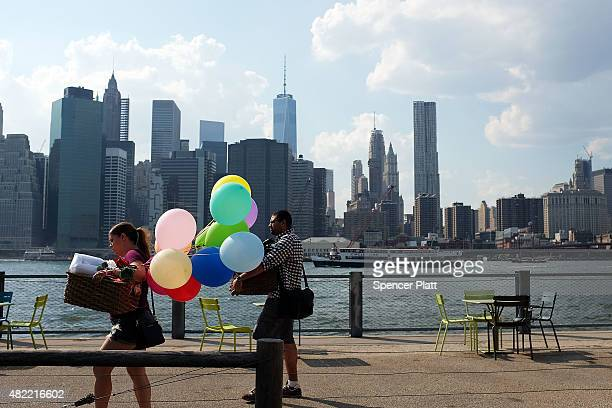 A woman walks with balloons to a picnic along the East River on a sweltering hot afternoon on July 28 2015 in New York City With temperatures in the...