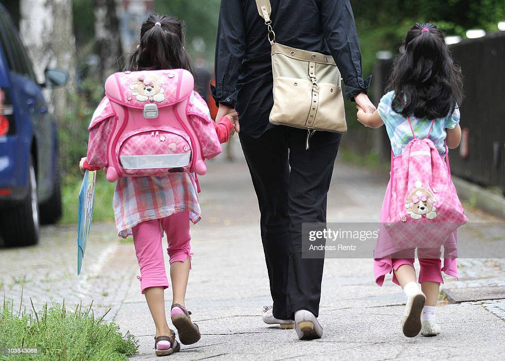 A woman walks with children to school on the first school day on August 23, 2010 in Berlin, Germany. Many German school districts, including those in Berlin, are reducing the school time span from 13 to 12 years as part of a nationwide set of primary and secondary school reforms..