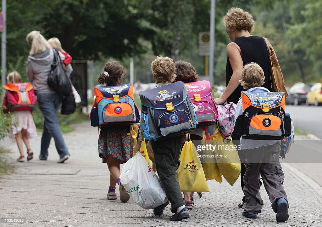 A woman walks with children to school on the first school day on August 23, 2010 in Berlin, Germany. Many German school districts, including those in Berlin, are reducing the school times pan from 13 to 12 years as part of a nationwide set of primary and secondary school reforms..