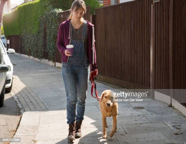 Woman walks with dog on lead and coffee in hand in residential street.