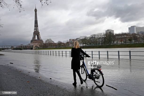 Woman walks with her bike on the flooded banks of the river Seine near the Eiffel Tower on February 02, 2021 in Paris, France. Heavy rains caused the...