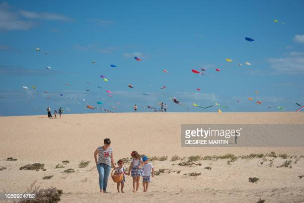 A woman walks with her children as some 450 professional and amateur kitefliers from eight different countries meet on the beaches of the Corralejo...
