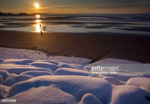 A woman walks with her dog at Higgins Beach shortly after sunrise on Thursday Jan 18 2018