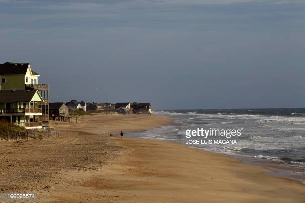 A woman walks with her dog in Rodanthe North Carolina as Hurricane Dorian make it's way to Cape Hatteras on September 5 2019 Hurricane Dorian lashed...