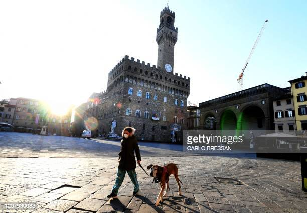 Woman walks with her dog on a deserted Piazza della Signoria in Florence on March, 21 2020, as part of the measures taken by Italian government to...