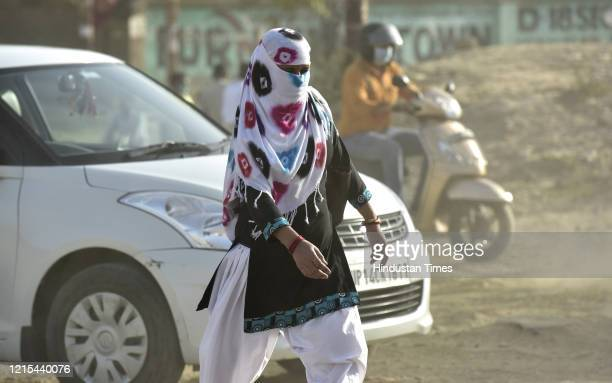 Woman walks with her head covered with cloth to protect from the sun on a hot summer day at Sector 69, on May 26, 2020 in Noida, India. A heat wave...