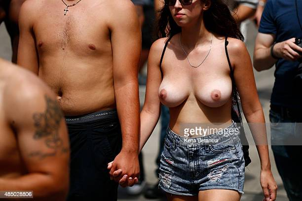 A woman walks with her partner as she bares her breasts in the GoTopless pride parade in Manhattan August 23 2015 in New York City The GoTopless...