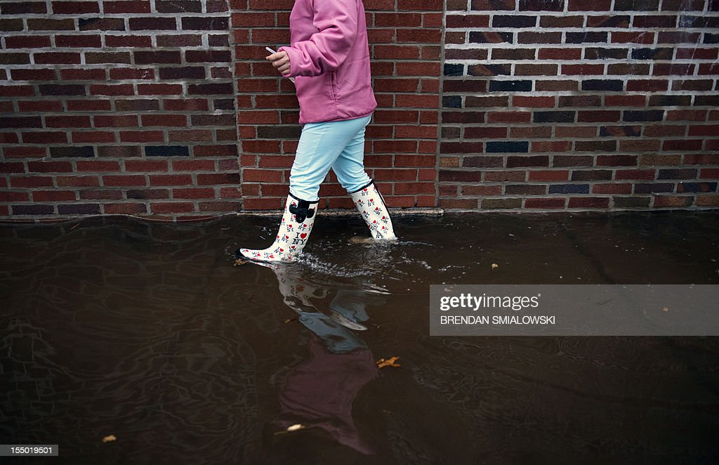 A woman walks with 'I Love New York' boots through flood water October 30, 2012 in Little Ferry, New Jersey. Hurricane Sandy which hit New York and New Jersey left much of Bergen County flooded and without power. AFP PHOTO/Brendan SMIALOWSKI