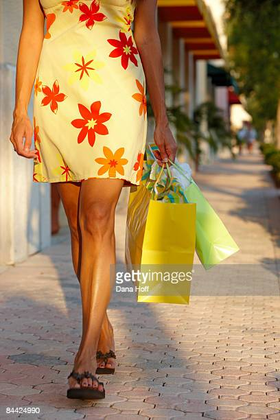 woman walks with shopping bags - palm beach county stock photos and pictures