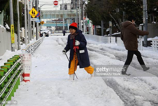 A woman walks with sticks on a snow covered road in Tokyo on February 9 2014 one day after a heavy snowfall hit the capital The heaviest snow in...