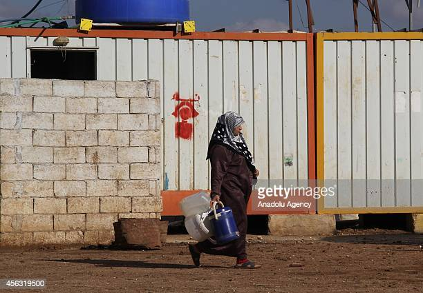 Woman walks with water bins and buckets at the tent city close to Al Salama border gate in Azez district of Aleppo, Syria on September 29, 2014.