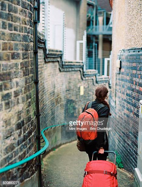 A woman walling down a narrow street, pulling a suitcase and holding an orange backpack.