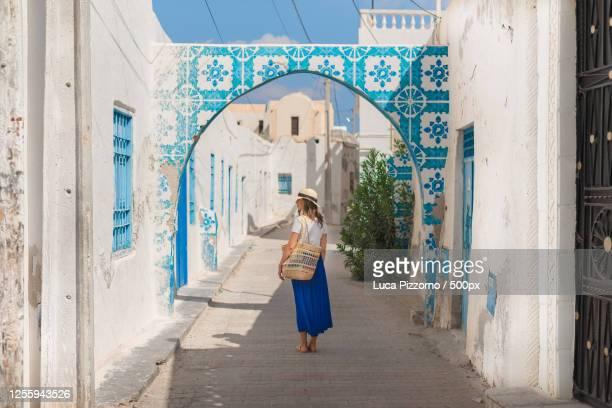 woman wandering around djerba, houmt souk, tunisia - djerba stockfoto's en -beelden