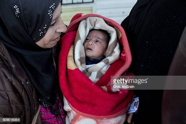 A woman wanting to leave Turkey holds her baby as she waits in line to pass through a border gate as a small number of Syrian refugees were allowed...