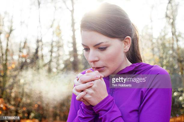 Woman warming hands on cold day.