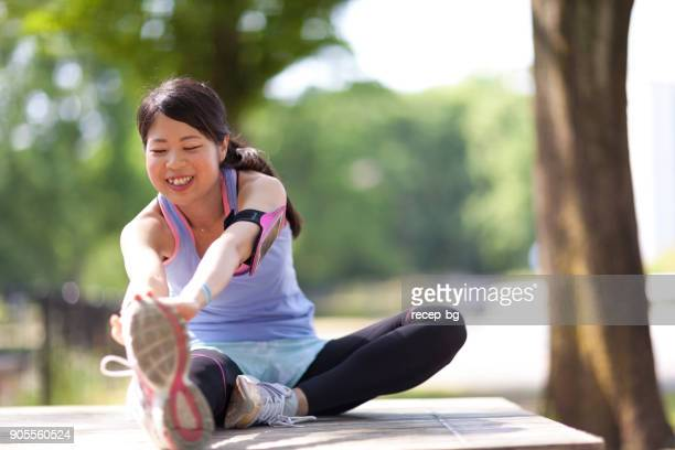 woman warming up before running - asian six pack stock photos and pictures