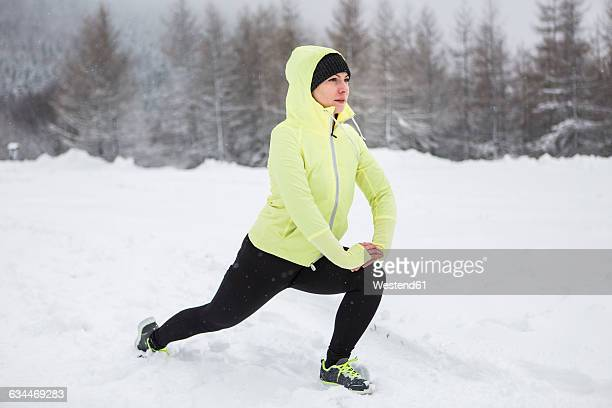 Woman warming up for cross country run in winter