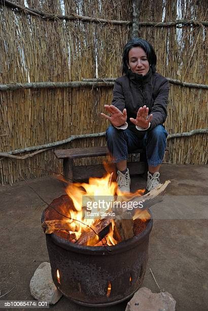 Woman warming up hands near brazier in hut