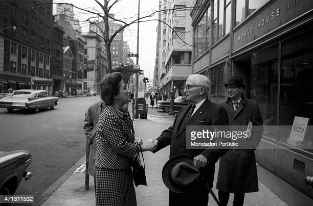 A woman warmly shakes the politician Harry Truman's hand who is walking on a footpath although his presidential term of office is ended in 1953 the...