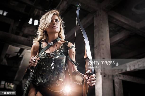 Woman warrior holding archery and taking out dagger.
