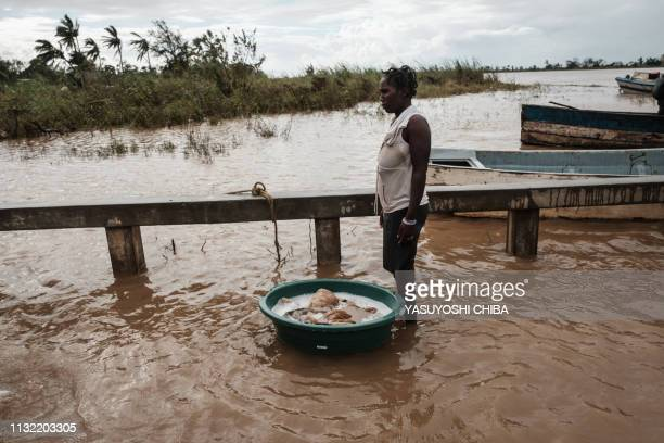A woman washes a blanket in muddy waters at a boat landing place in Buzi Mozambique on March 23 2019 The death toll in Mozambique on March 23 2019...