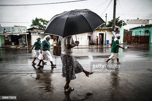 TOPSHOT A woman washes a her foot with water streaming out of a pipe as catholic nuns leave the St Michel Church in Libreville on August 28 2016...
