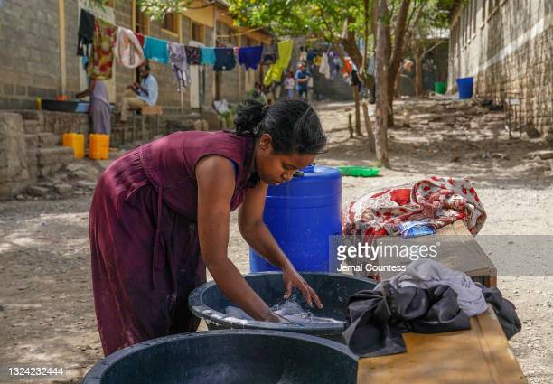 Woman washes and hangs cloths at the IDP camp at the Kisanet Complete Primary and Junior school IDP community on June 18, 2021 in Mekele, Ethiopia....