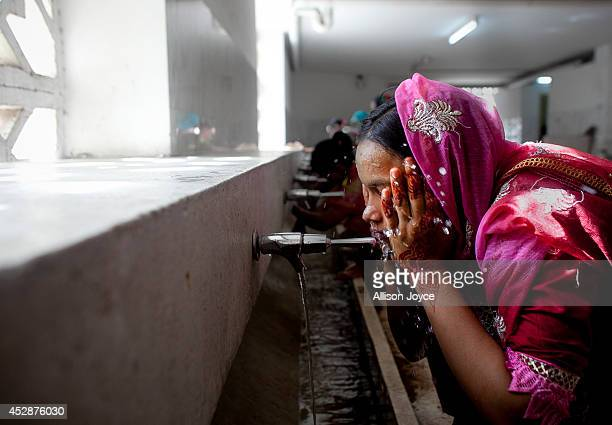 A woman washes before praying at the National Mosque Baitul Mukarram during Eid alFitr on July 29 2014 in Dhaka Bangladesh Muslims around the world...