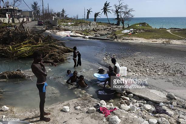 TOPSHOT A woman washes clothes and children take a bath in the streets of PortSalut southwest of PortauPrince in Haiti on October 9 following the...