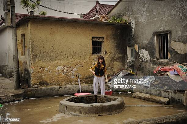 Woman washes clothes from well water in Wukan where voting in village elections is taking place on March 4, 2012. The Chinese village that rebelled...