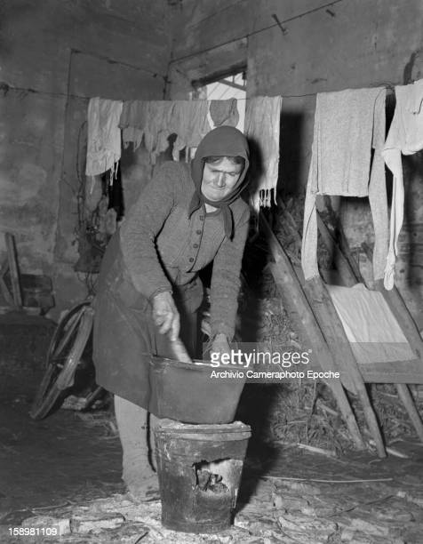 A woman washes clothes in a bucket heated by coal Comacchio Italy 1949