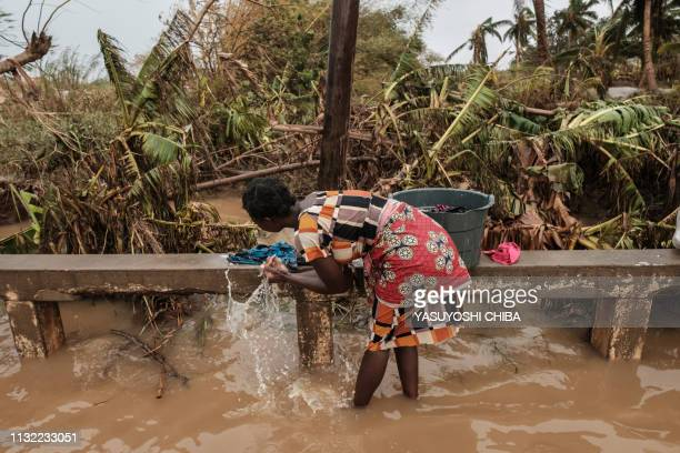 A woman washes clothes in muddy waters at a boat landing place in Buzi Mozambique on March 23 2019 The death toll in Mozambique on March 23 2019...