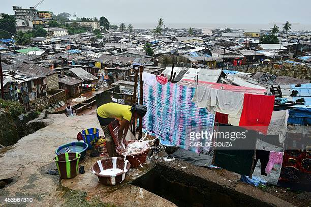 A woman washes clothes in the Kroo town slum in Freetown on August 13 2014 The World Health Organisation revealed that the latest death toll from the...