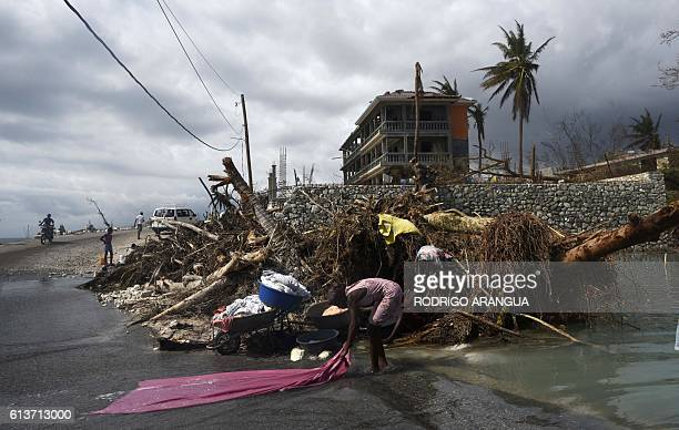 TOPSHOT A woman washes clothes in the streets of PortSalut southwest of PortauPrince in Haiti on October 9 following the passage of Hurricane Matthew...