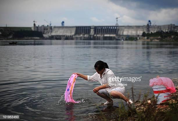 A woman washes clothes near the Danjiangkou Reservoir Dam on June 9 2010 in Danjiangkou of Hubei Province China Mass migration has been started in...