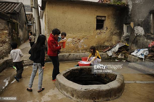 Woman washes clothes next to a well whilst children play in Wukan where voting in village elections is taking place on March 4, 2012. The Chinese...