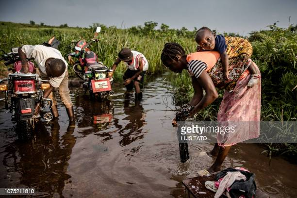 A woman washes clothes while relatives wash their motorbikes in a stream in a remote area near MbanzaNgungu Democratic Republic of Congo on December...