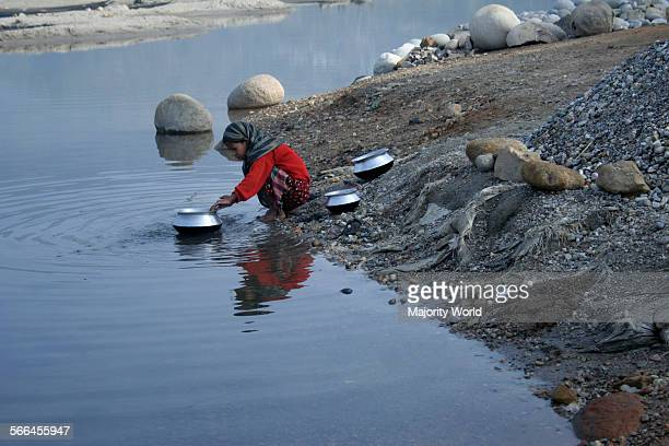 A woman washes cooking pots on the bank of Dauki river Jaflong Sylhet Bangladesh January 18 2010