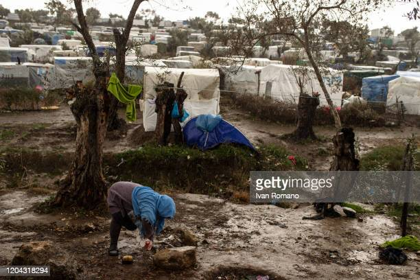 Woman washes dishes near her tent in the Moria refugee camp on February 5, 2020 in Moria, Greece. About 19,000 migrants from Afghanistan, Syria and...