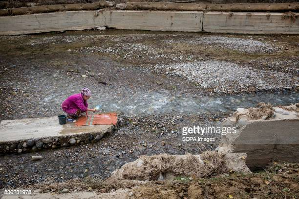 A woman washes her carpet in the river which is also the source of drinking water for villagers in Beshkent Kyrgyzstan The water they drink is...