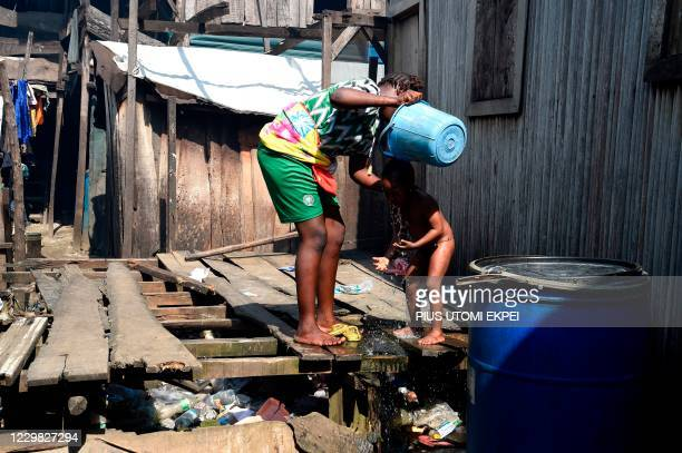 Woman washes her child in a makeshift home in the Makoko riverine slum settlement in Lagos on November 27, 2020. - The United Nations World Food...