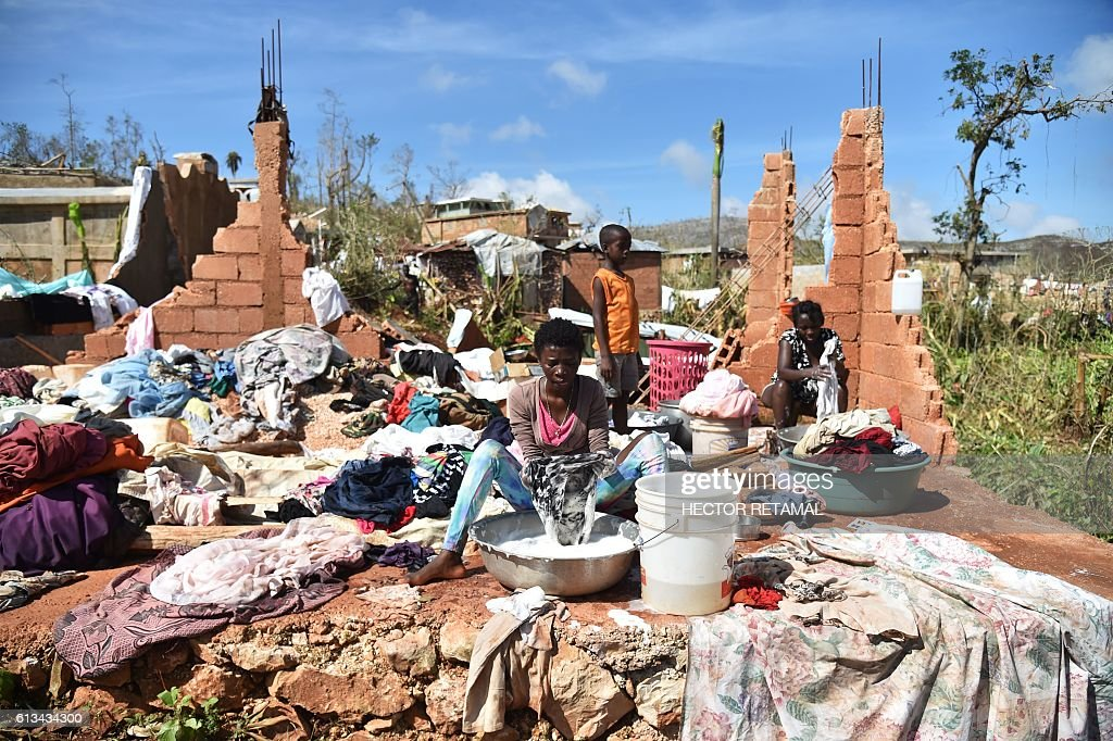 TOPSHOT - A woman washes her clothes in the middle of her home destroyed by Hurricane Matthew, in the small village of Casanette, Haiti, on October 8, 2016. The full scale of the devastation in hurricane-hit rural Haiti became clear as the death toll surged over 400, three days after Hurricane Matthew leveled huge swaths of the country's south. / AFP / HECTOR