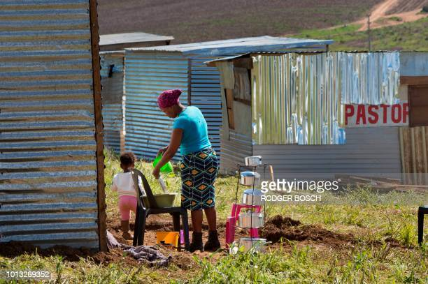 A woman washes her dishes outside her recentlybuilt shack on a piece of land belonging to the Louiesenhof Wine Estate on August 8 in Stellenbosch...