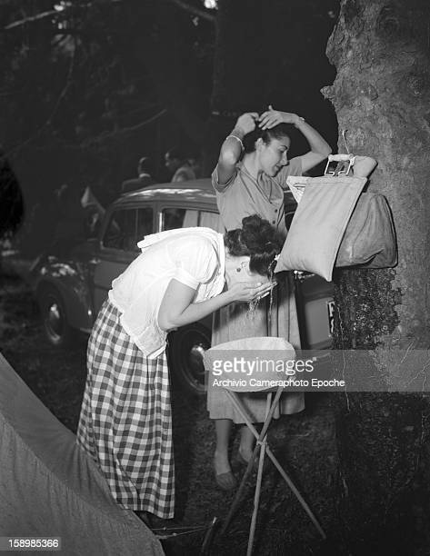 A woman washes her face while a second woman combs her hair outside a tent at a campsite Padova Italy 1950