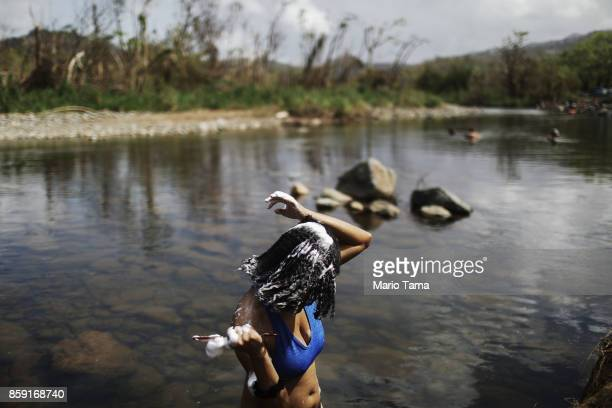 A woman washes her hair in the Espiritu Santo river along hurricanedamaged forest more than two weeks after Hurricane Maria hit the island on October...