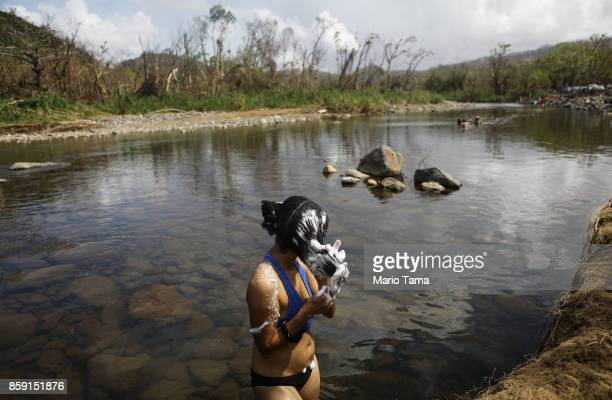 A woman washes her hair in the Espiritu Santo river more than two weeks after Hurricane Maria hit the island on October 8 2017 in Palmer Puerto Rico...