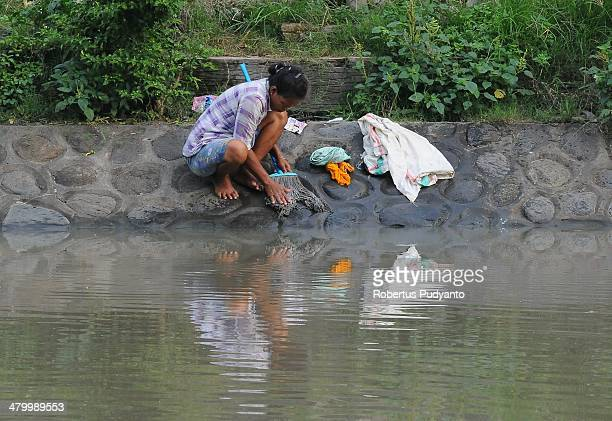 A woman washes her household appliances in a polluted river on World Water Day March 22 2014 in Surabaya Indonesia World Water Day recognizes the...